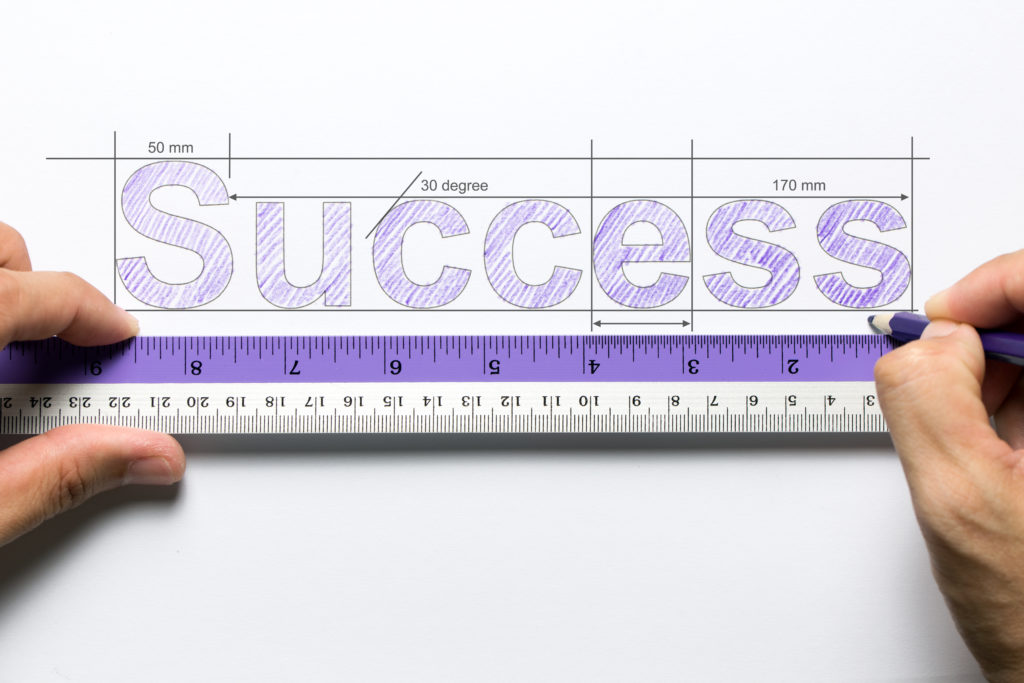 Hand holding ruler and pencil measuring the word success
